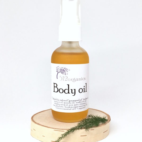 512organics body oil on wood slice with fern